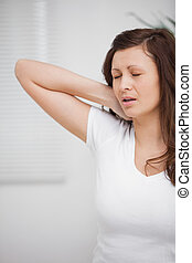 Woman touching her painful neck in a room