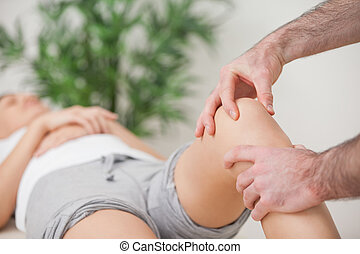 Practitioner using his fingers to massage a knee in a room