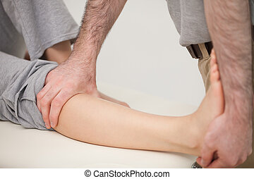 Physiotherapist stretching the leg of a patient