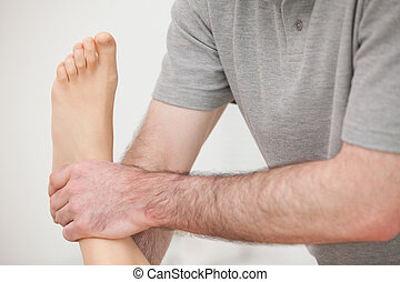 Close-up of a physiotherapist manipulating an ankle in a...