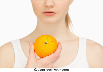 Woman holding an orange against white background