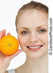 Fair-haired woman presenting an orange against white...