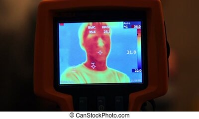 Hand hold thermal image camera, on-screen human face, hands...