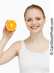 Smiling woman holding an orange against white background