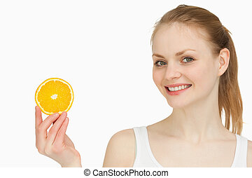 Cheerful woman holding an orange slice against white...