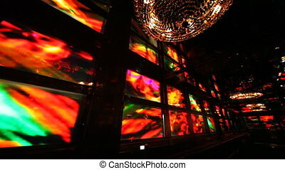 wall displays rhythmically flashing colored lights in corner nightclub