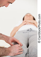 Woman lying on her back while a physiotherapist massing her...
