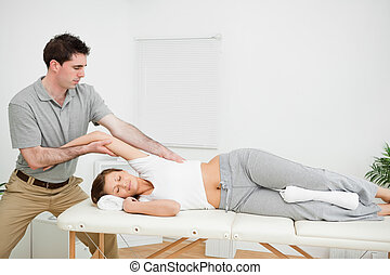 Chiropractor stretching the arm of his patient while holding...