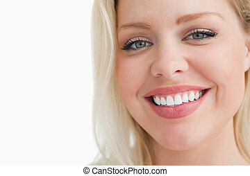 Smiling blonde woman staring at the camera against a white...
