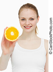Woman holding an orange while smiling against white...