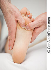 Chiropodist massaging the foot of a patient in a medical...