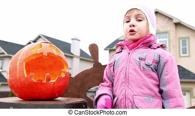 Little girl speak and show on pumpkin of Halloween at...