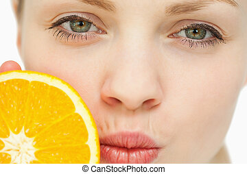 Close up of a woman placing an orange near her mouth against...