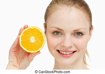 Close up of a smiling woman presenting an orange against...