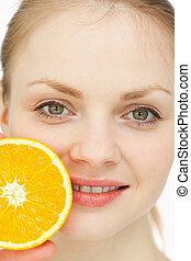 Close up of a woman placing an orange on her lips