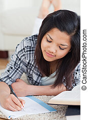 Woman lying on the floor while writing on a notebook