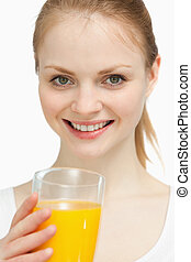 Smiling woman holding a glass of orange juice against white...