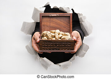 Hand breakthrough wall holding golden nuggets in treasure chest means breakthrough in finance or similar things - one of the breakthrough series