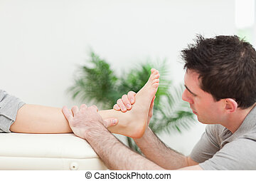 Physiotherapist sitting while massaging a foot