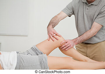 Knee of a woman being massaged by a physiotherapist in a...