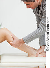 Serious osteopath holding the calf of a patient