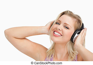 Blonde woman raising her arms while listening to music...