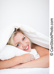 Young smiling woman embracing a pillow