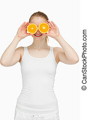 Joyful woman placing oranges on her eyes against white...