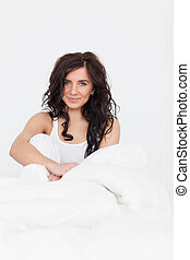 Peaceful woman sitting in her bed while waking up