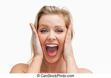 Happy blonde woman standing while showing her surprise