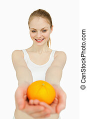 Woman presenting a tangerine while looking at it against...