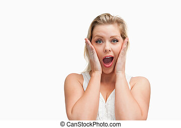 Surprised blonde woman putting her hands on her cheeks