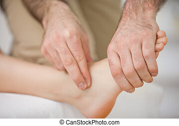 Two fingers touching and massaging a foot