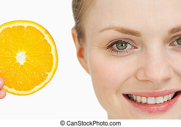 Close up of a woman presenting an orange slice against white...
