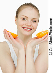 Close up of a smiling woman holding oranges against white...