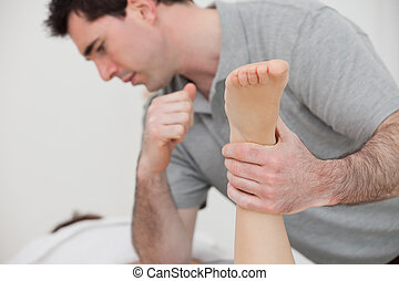 Physio manipulating the leg of a patient