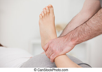 Physiotherapist manipulating an ankle indoors