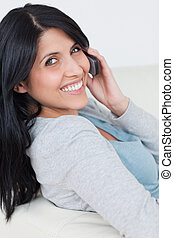 Woman smiling while holding a phone next to her ear