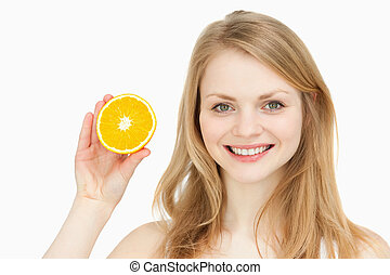 Joyful woman presenting an orange against white background