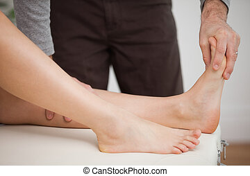 Chiropodist touching the foot of a patient in a room