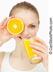 Woman placing an orange on her eye while drinking in a glass...