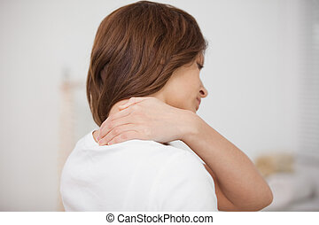 Brown-haired woman massaging her painful neck in a room