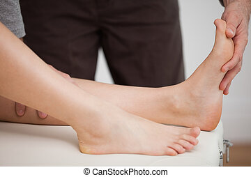 Physiotherapist manipulating the foot of a patient in a room