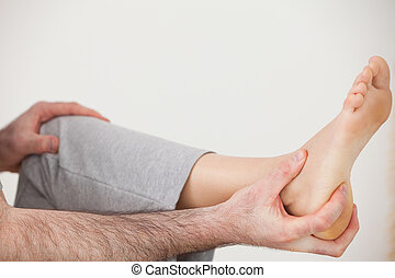 Chiropractor holding the heel of a patient