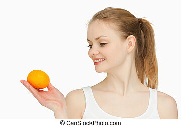 Woman holding a tangerine while looking at it against white...
