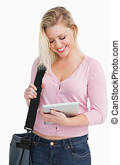 Happy blonde woman holding her tablet pc
