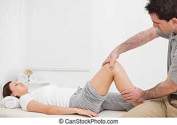 Brunette woman lying while a physiotherapist manipulates her...