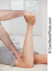 Physiotherapist bending the led of a woman