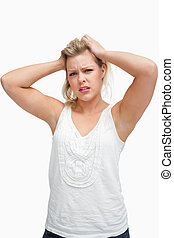 Upset woman frowning while placing her hands on her head