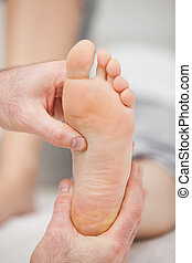 Doctor pressing the sole of a foot with his thumb in a room